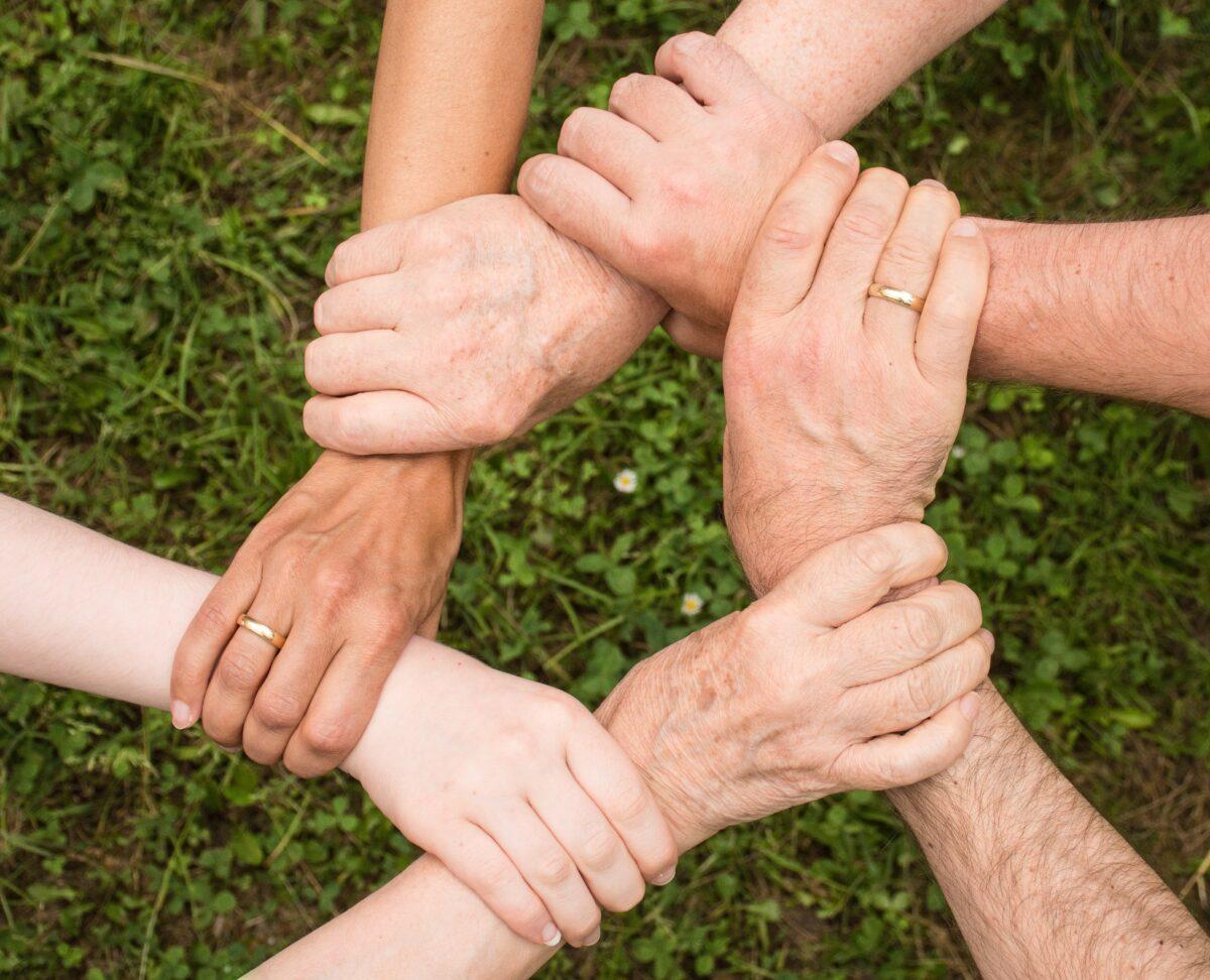 Kuusi ihmistä pitää toisiaan kädestä yhteistyön merkiksi